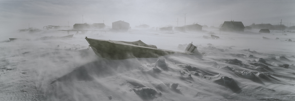 Toksook Bay, Alaska –  A winter's storm howls through the town, making a beached boat appear as though it is crashing through waves.