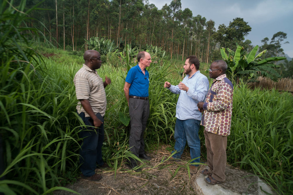 Tom Smolich, S.J., director of JRS discusses the possible site for a new school with fellow Jesuits, Martin Buhati, Luis Vizcaino, and Dieudonné Kapita.