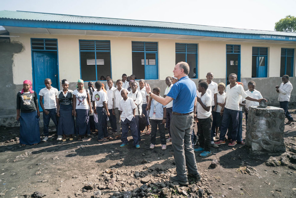Tom Smolich, SJ, met with school students outside of Goma, in the Congo. JRS built the school and pays their tuition.