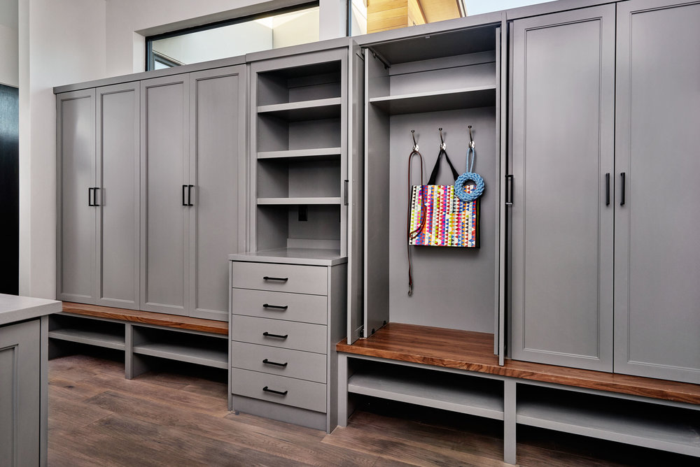 "Here, Collin used pocket doors on ""locker-style"" cabinetry to keep them out of the way when they need to be open. He also utilized an open cabinet space and added electrical outlets for a family ""charging station."""