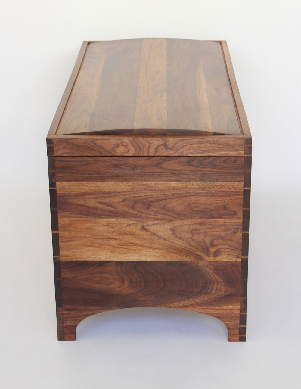The side profile of the chest shows the graduated dovetails, as well as the arc of the panel top and the leg cutaway