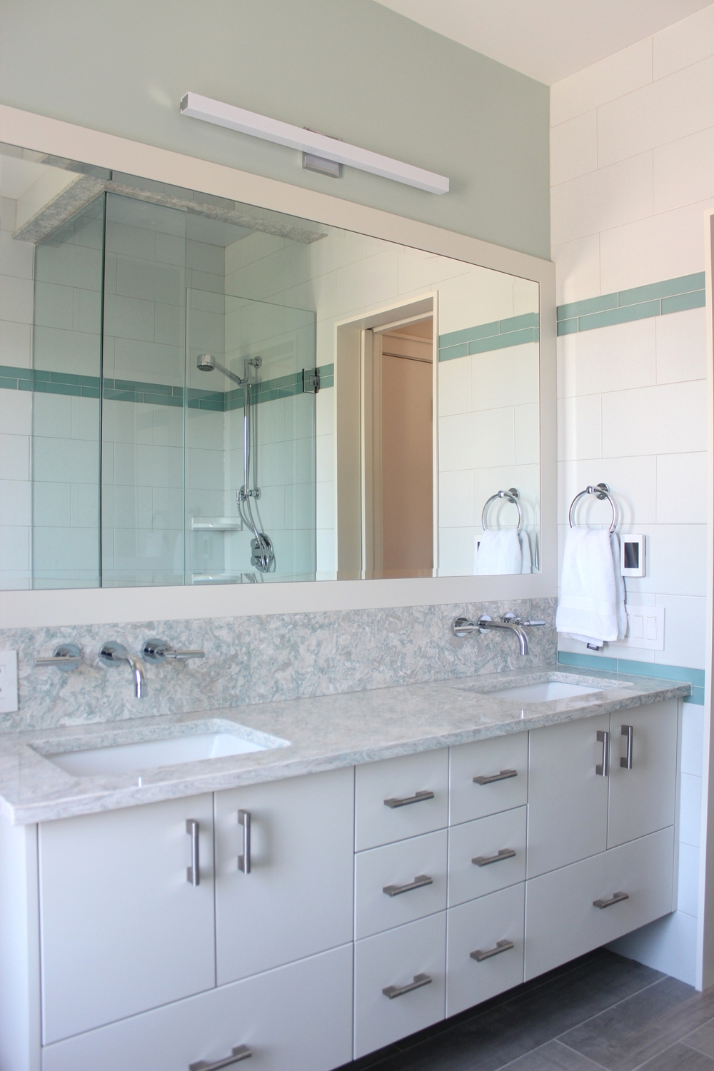 Kids bath with modern cabinets, a HUGE custom mirror and Cambria countertop and backsplash to tie it all together.