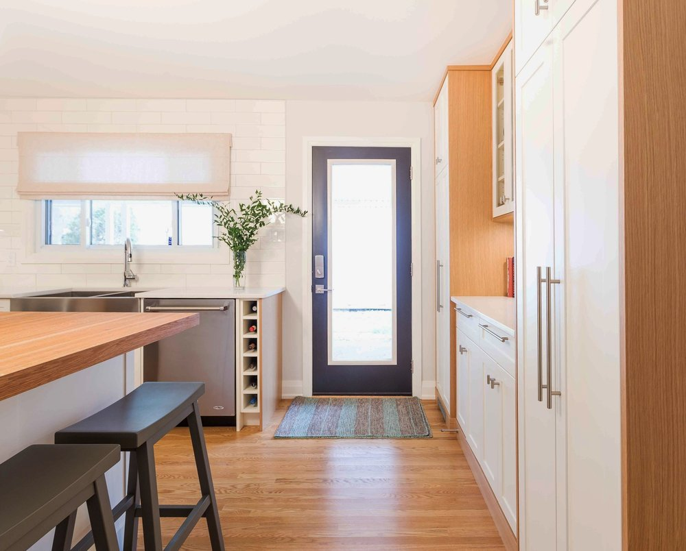 The cabinetry to the right of the side entrance covers many necessities: coat storage, bar glasses and liquor storage and a full height pantry with roll out drawers.