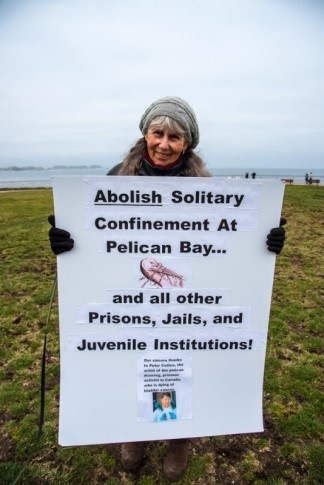 "Phyllis Greenleaf: ""Abolish Solitary Confinement at Pelican Bay…and all other Prisons, Jails, and Juvenile Institutions! Our sincere thanks to Peter Collins, the artist of the pelican drawing, prisoner activist in Canada, who is dying of bladder cancer,"" with the pelican, beak in chains, that he drew for the Prisoner Hunger Strike. We asked people to write letters for his Compassionate Release. [UPDATE: Refused compassionate release, Peter died in prison on August 13, 2015, the day after Hugo Yogi Bear Pinell was assassinated. ¡Pete Collins, Presente!]"
