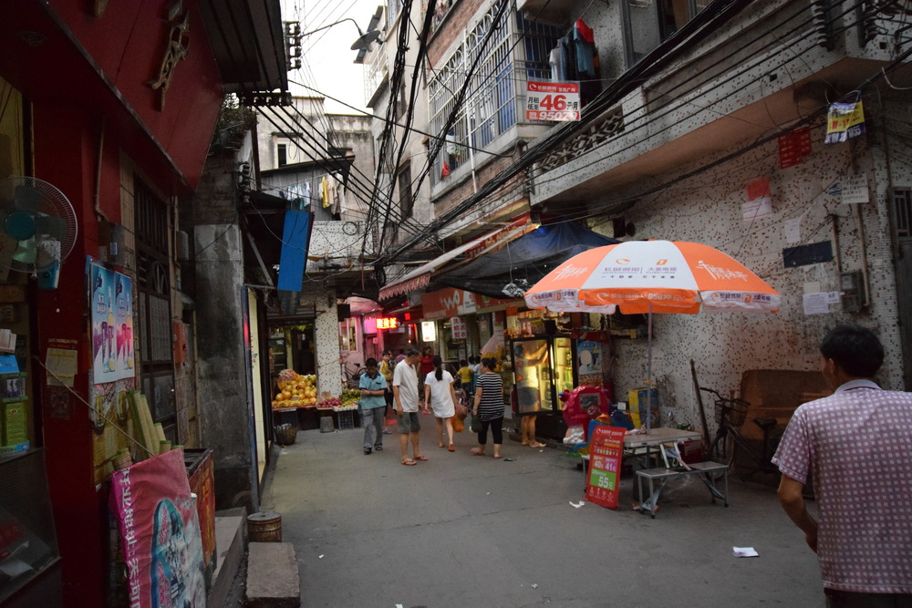 A restaurant, a fruit store & electric cables hanging from all over the place. A typical back street in China.