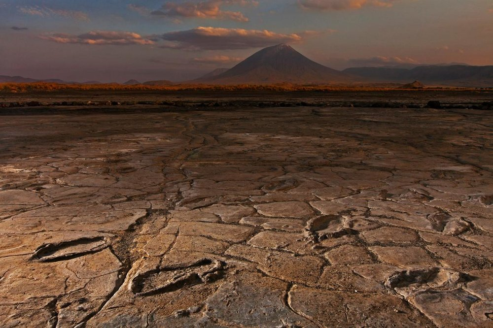 Mudflats in the shadow of the Ol Doinyo Lengai volcano captured a huge trove of ancient human footprints.  PHOTOGRAPH BY ROBERT CLARK, NATIONAL GEOGRAPHIC CREATIVE