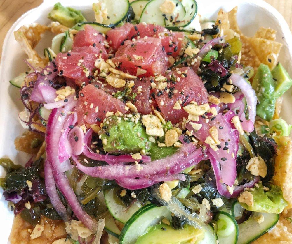 Poke Nachos - Crispy wontons, Ahi Tuna, Avocado, Scallions, Crispy garlic, Cucumber, Seaweed Salad, Hawaiian Sea Salt, tomato, pickled red onion, Creamy Togarashi & Unagi Sauce