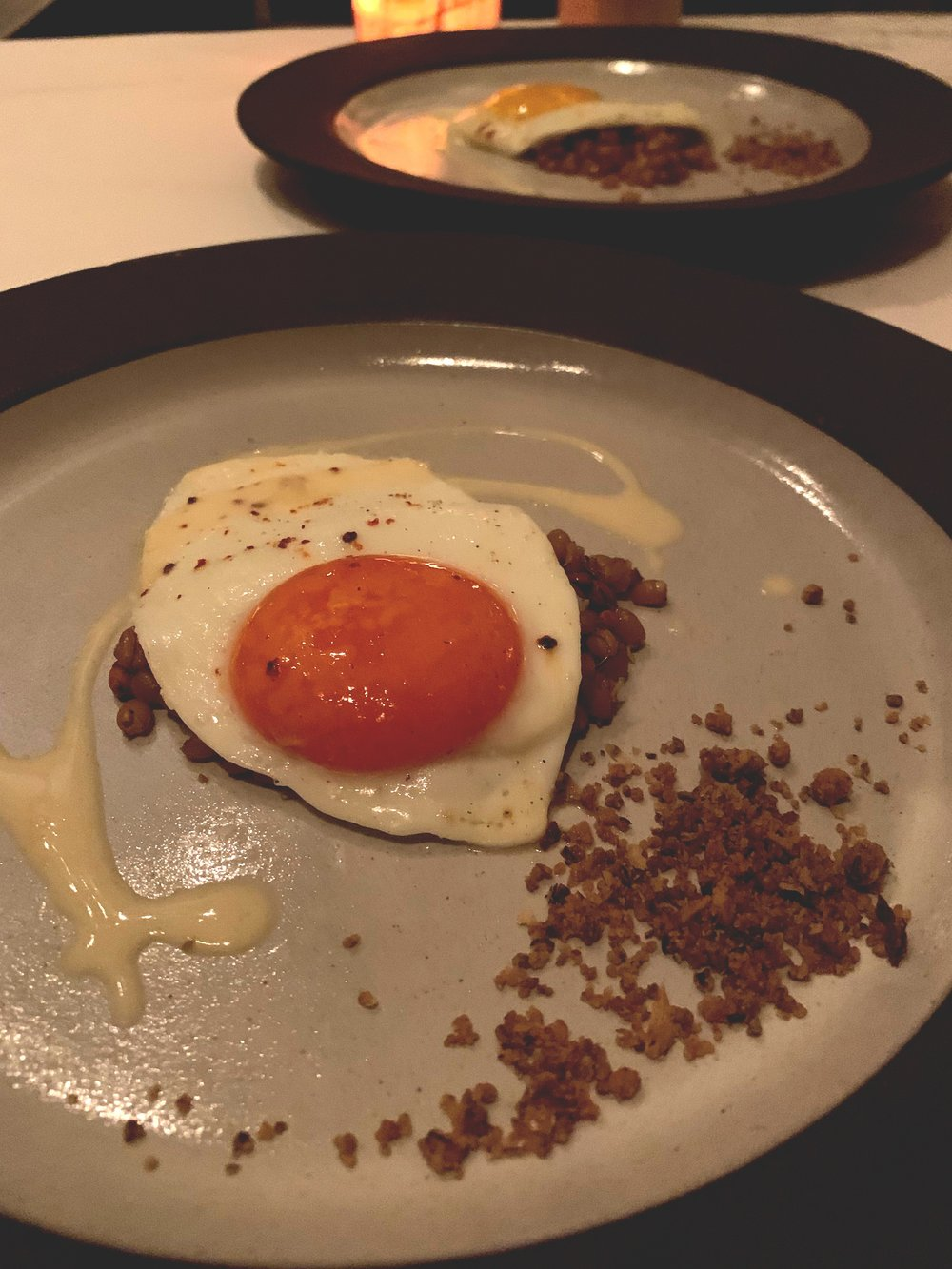 "Red Pepper egg, Nash's Rye, and Cheddar - A few dishes before this, a chef walks out and says that we are going to play a game. Some of the hens on the farm had been feed grains with red pepper, turning their yolks red. This was done in an effort to prove ""you are what you eat.""Two raw, shelled eggs were presented, and one had red yolk inside and one was regular. We were asked to pick an egg and brand it somehow with a Sharpie to show it was ours. I let Yvonne pick first, because i'm a gentlemen. She ended up picking the regular yellow egg, so I got to have the red pepper one. The flavor of this egg was so amazing, and the pairing with the rye and cheddar just blew me away.This was the outstanding dish of the night for me and the one that I thought epitomized Blue Hill the best. If you didn't know the story, you would think this is just an egg, but literally from the hen to the plate, every flavor was beautifully planned to the nth degree."