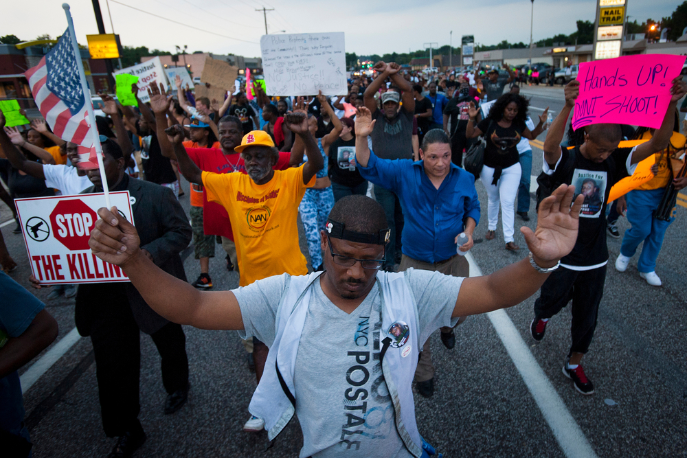 Protestors march down W. Florissant Ave. in Ferguson, Mo., on the evening of August 16, a week following the police shooting of Michael Brown Jr. Members of the New Black Panther Party had negotiated an informal agreement with police to shut down W. Florissant so protestors could march.