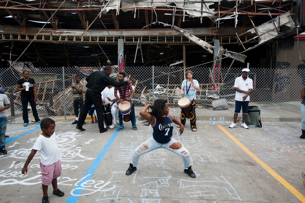 Drummers and dancers gather outside the burnt-out hulk of the QuikTrip gas station that served as a staging ground for protestors in Ferguson, Mo. False rumor was that the owner of the QuikTrip had called the police on Michael Brown.