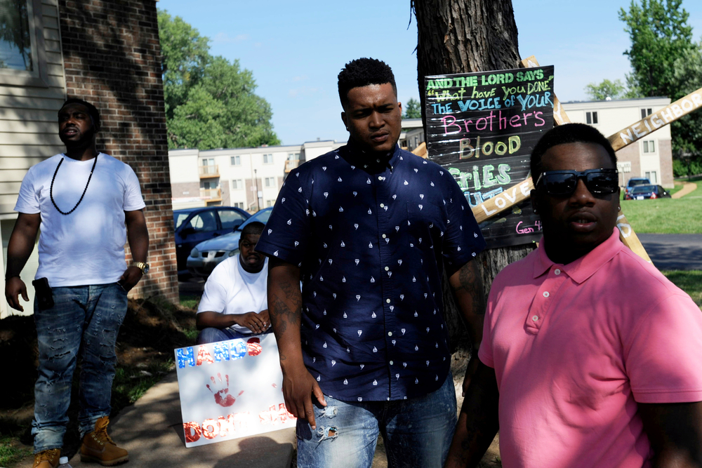 A number of young men from who grew up in the Ferguson neighborhood and surrounding areas returned to the city after the police shooting death of Michael Brown, stopping to pay their respects at the site of Brown's death on Canfield Ave.