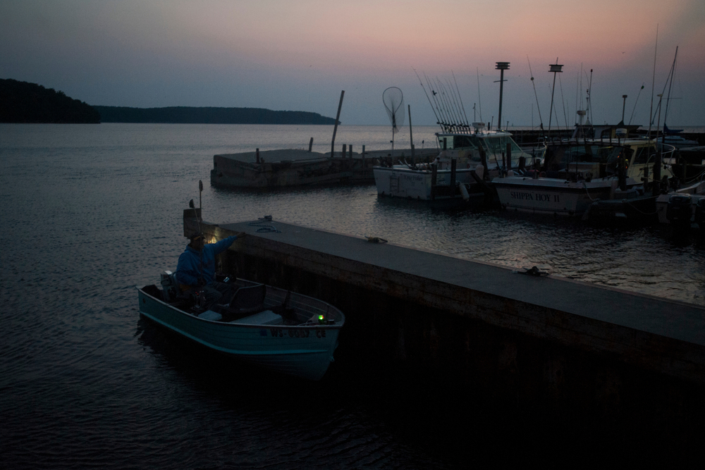 Peter Berns, a friend of Eric Weborg, pilots his small boat in after the sun sets on steelhead salmon fishing. Peter and Eric fished off Death's Door and returned to the docks that the Weborgs own and rent out to people who then do fishing trips for tourists.