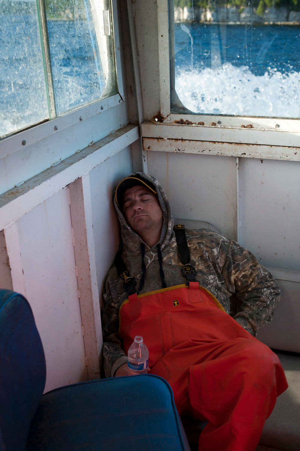Eric Weborg sleeps on the Robyn B. as the crew heads out to pull nets. The crews fish 3-4 times a week, starting early in the morning, depending on orders or the number of fish caught on previous days.