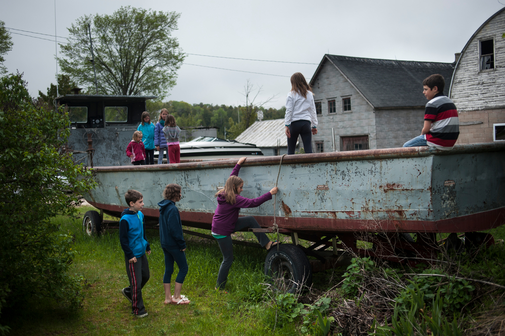 Kids play on a trap net fishing boat, laid up in disrepair in part to a shortage of crew to run the boat. The boat belongs to Rick Johnson who now fishes with the Weborg family since the downturn in the fishing market.
