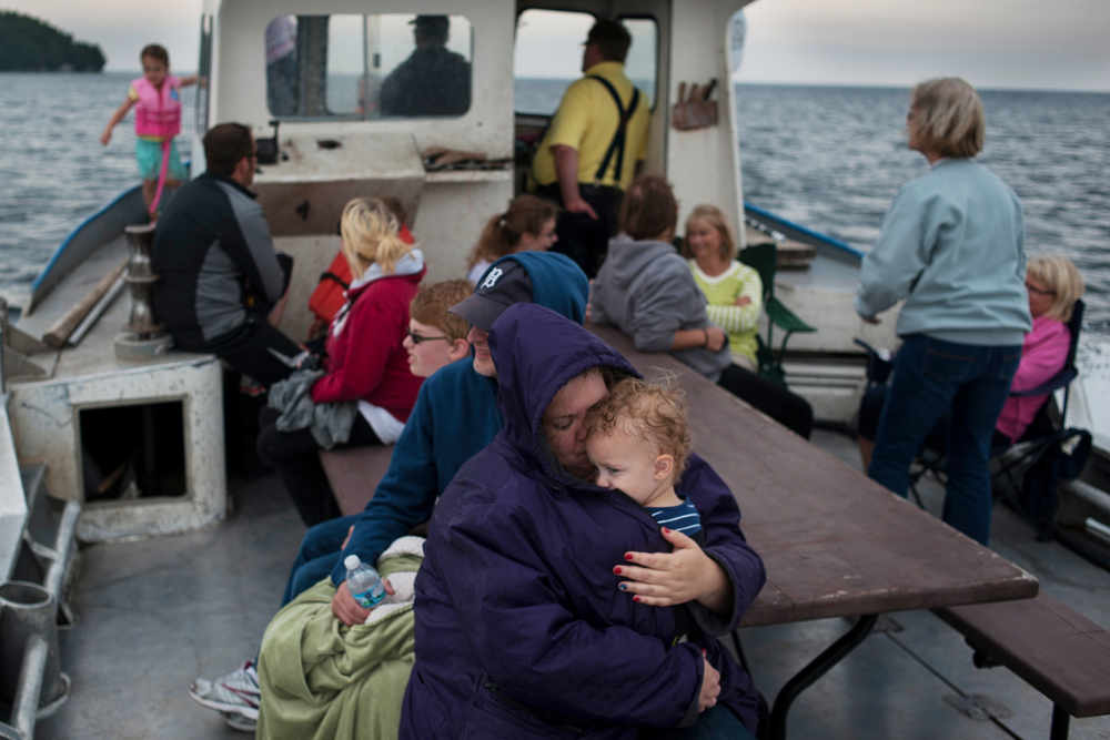 Out on the water on one of the family boats, the Heather J., Heather Knop shields her daughter Molly from the weather  as Mark Weborg captains the commercial fishing boat for a family picnic.
