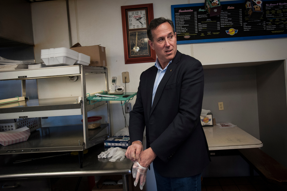 Republican presidential candidate Rick Santorum puts on gloves to help prepare lunch at Bob's Drive Inn for his campaign staff between campaign stops Le Mars, Iowa.