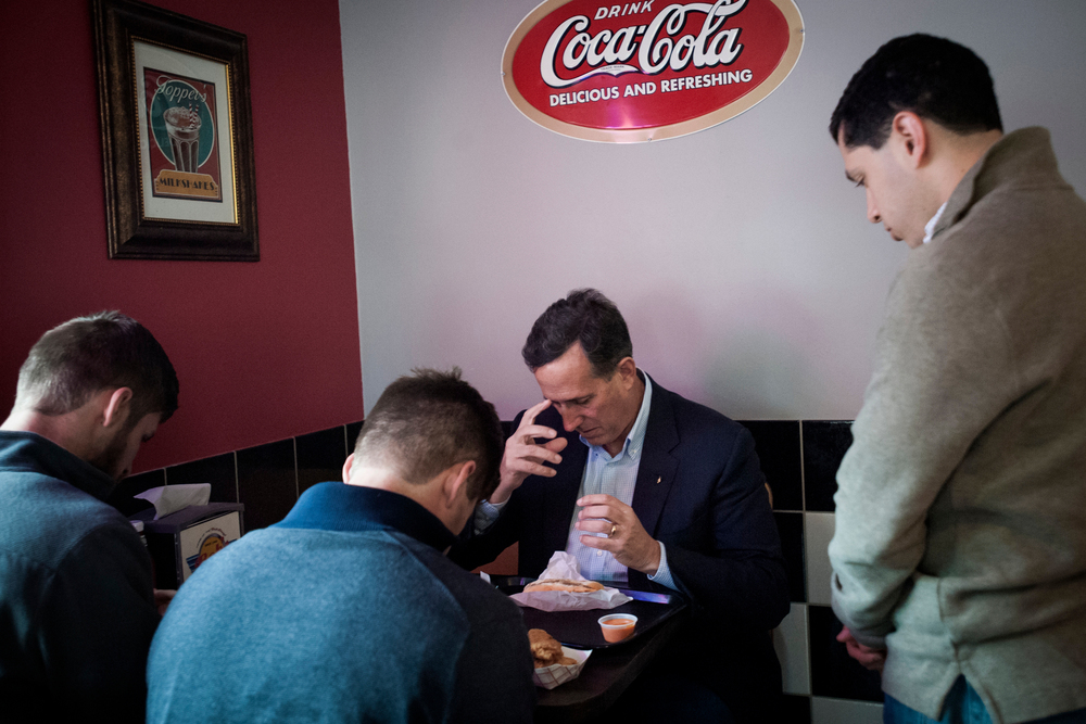 Republican presidential candidate Rick Santorum prays with his staff before lunch between campaign stops at Bob's Drive Inn in Le Mars, Iowa.