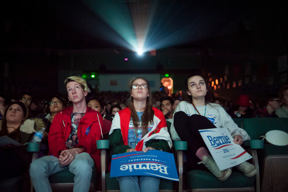 Jonah Guy (L), Deni Baird, and Lenin Cardwell watch a movie screen at a debate watch event in support of Democratic U.S. presidential candidate Bernie Sanders in Des Moines, Iowa November 14, 2015. REUTERS/Mark Kauzlarich
