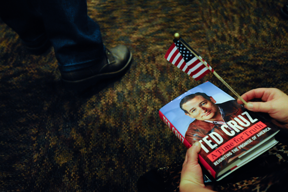 A supporter of U.S. Republican presidential candidate Ted Cruz holds a copy of his book (R) as Cruz speaks (L) at a campaign stop at a Pizza Ranch restaurant in Newton, Iowa November 29, 2015. REUTERS/Mark Kauzlarich