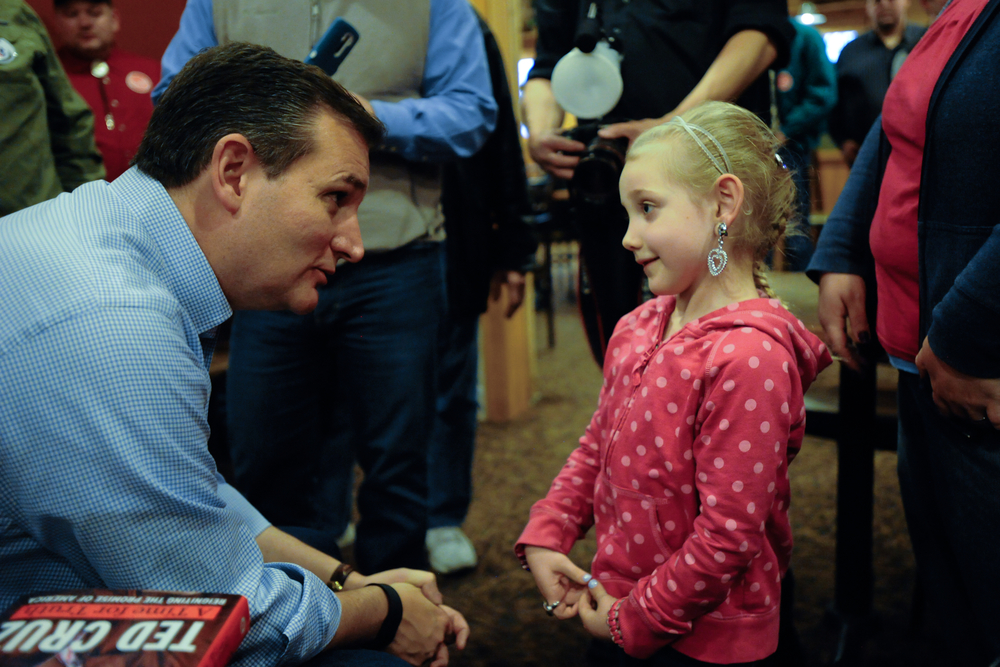 U.S. Republican presidential candidate Ted Cruz talks to Sally Vandall, 5, of Newton, Iowa at a campaign stop at a Pizza Ranch restaurant in Newton, Iowa November 29, 2015. REUTERS/Mark Kauzlarich