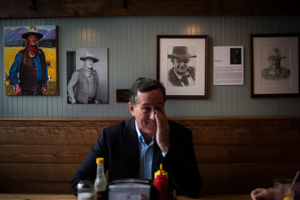 "U.S. Republican presidential candidate Rick Santorum sits in the ""John Wayne Memorial Booth"" at Northside Diner in Winterset, Iowa December 8, 2015. John Wayne was born in Winterset and his mark is everywhere in the town."