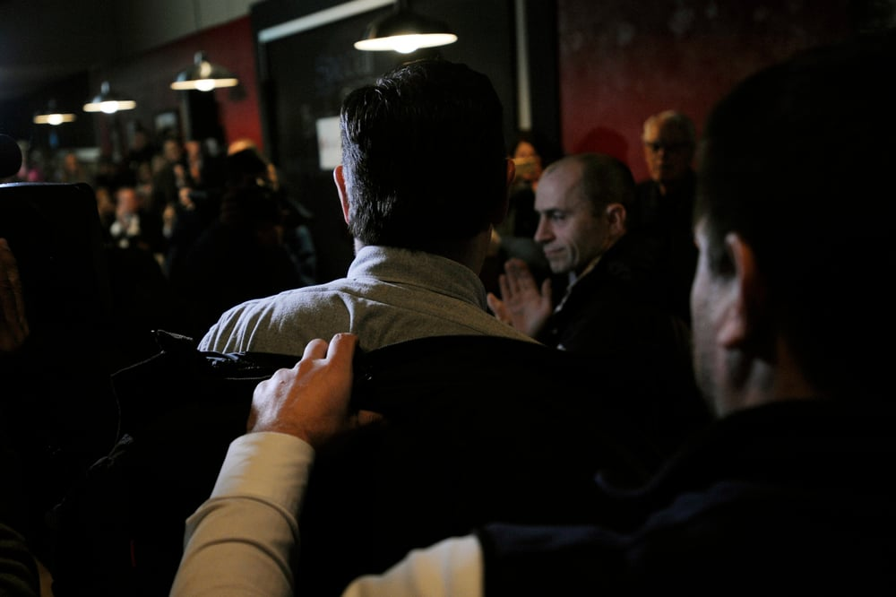 U.S. Republican presidential candidate Ted Cruz removes his jacket with the help of his body man Bruce Redden (R) at a campaign stop at Union Jacks Grill in Rock Rapids, Iowa January 6, 2016.