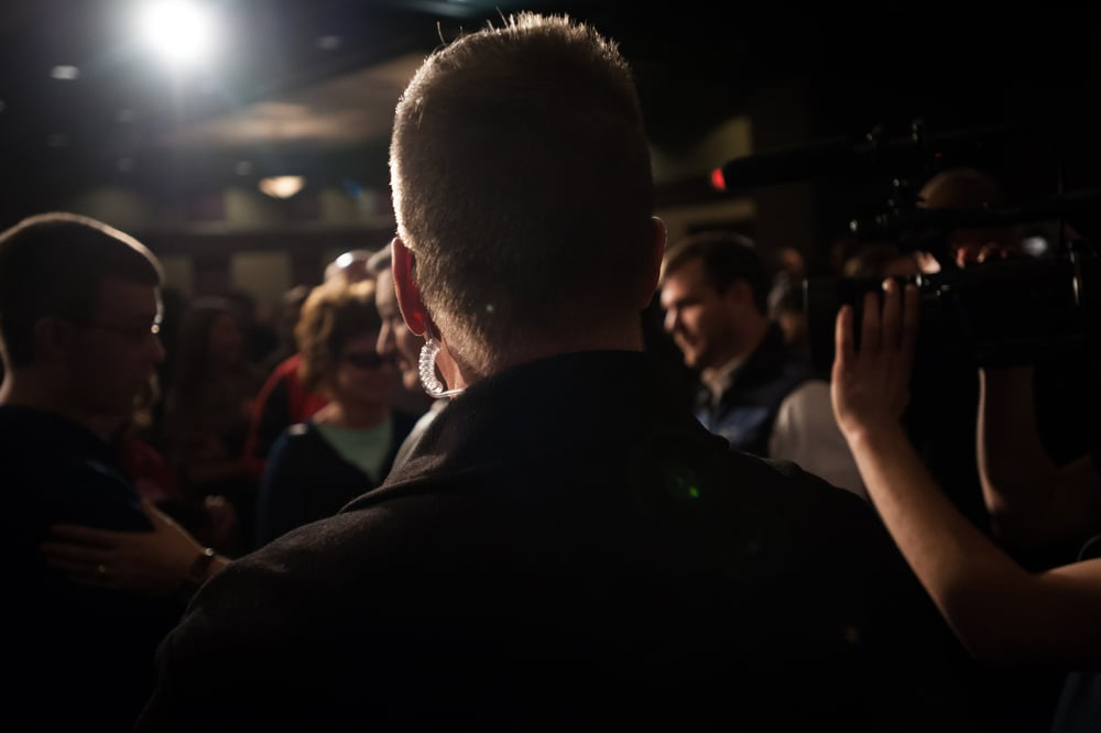 Private security watches the crowd as U.S. Republican presidential candidate Ted Cruz greets supporters after speaking at Clay County Regional Event Center Ballroom in Spencer, Iowa January 6, 2016.