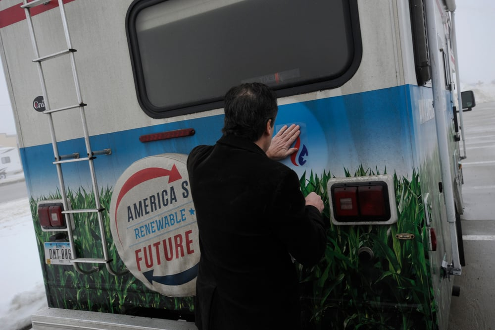 Rick Tyler, communications director for U.S. Republican presidential candidate Ted Cruz places a Ted Cruz logo sticker on the camper of America's Renewable Future, a pro-Ethanol group, in Storm Lake, Iowa January 7, 2016. The group handed out anti-Cruz literature at the first three days of his bus tour through Iowa, forcing Cruz to explain his position on energy subsidies.