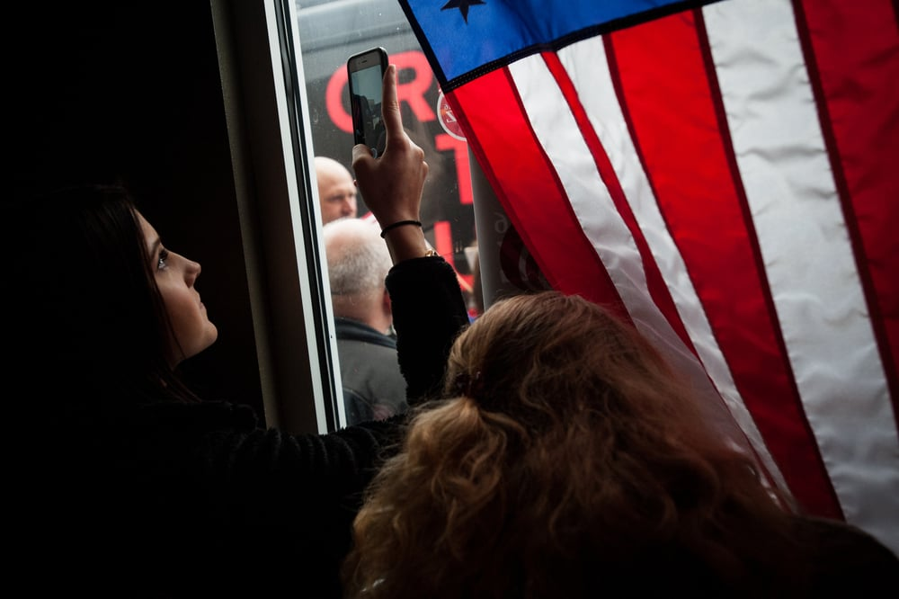 Jessica McQuiggen (L) and Rylee Eisenbartch peer out the window for a glimpse of U.S. Republican presidential candidate Cruz as he arrives at a Pizza Ranch restaurant in Pocahontas, Iowa January 7, 2016. REUTERS/Mark Kauzlarich