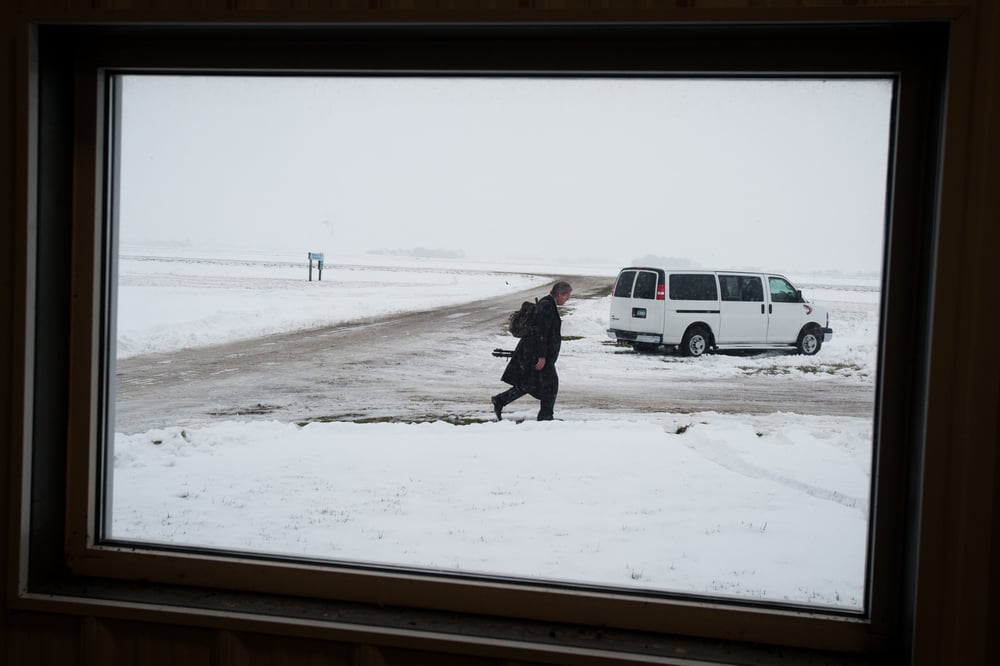 A reporter walks through the snow outside the window of an airplane hanger ahead of media availability for U.S. Republican presidential candidate Ted Cruz at the Webster City Municipal Airport in Webster City, Iowa January 7, 2016. REUTERS/Mark Kauzlarich
