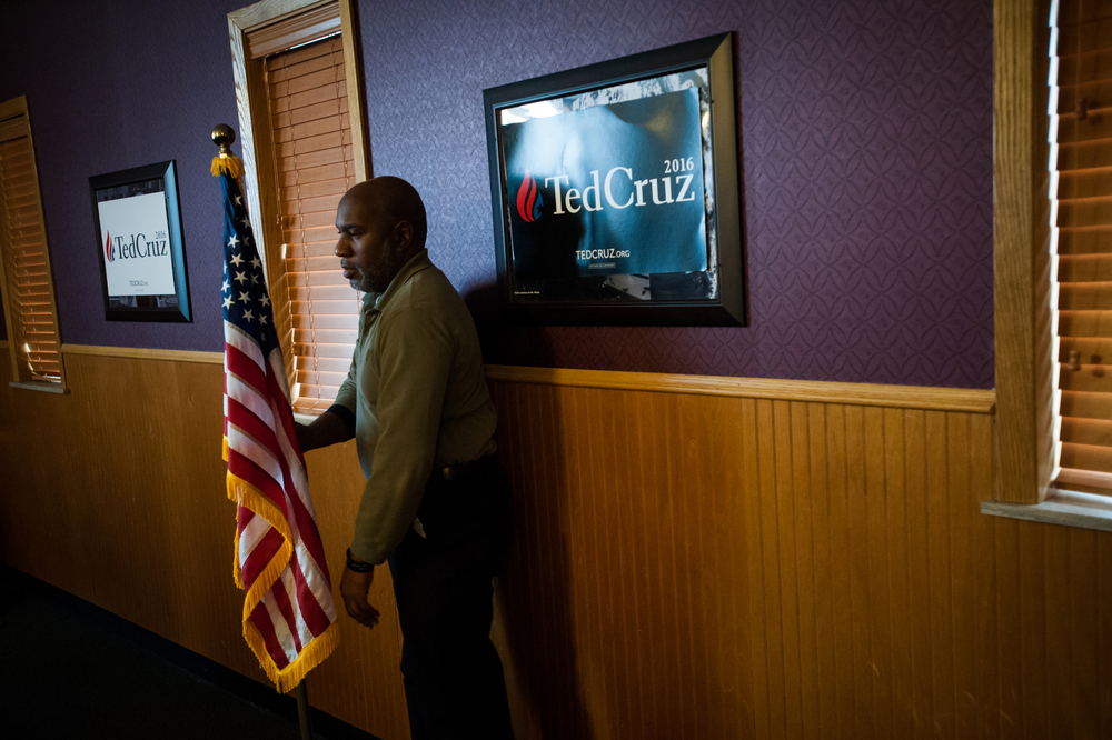A man adjusts a flag ahead of Republican U.S. presidential candidate Ted Cruz' campaign stop at Godfather's Pizza in Spirit Lake, Iowa on January 6, 2016.