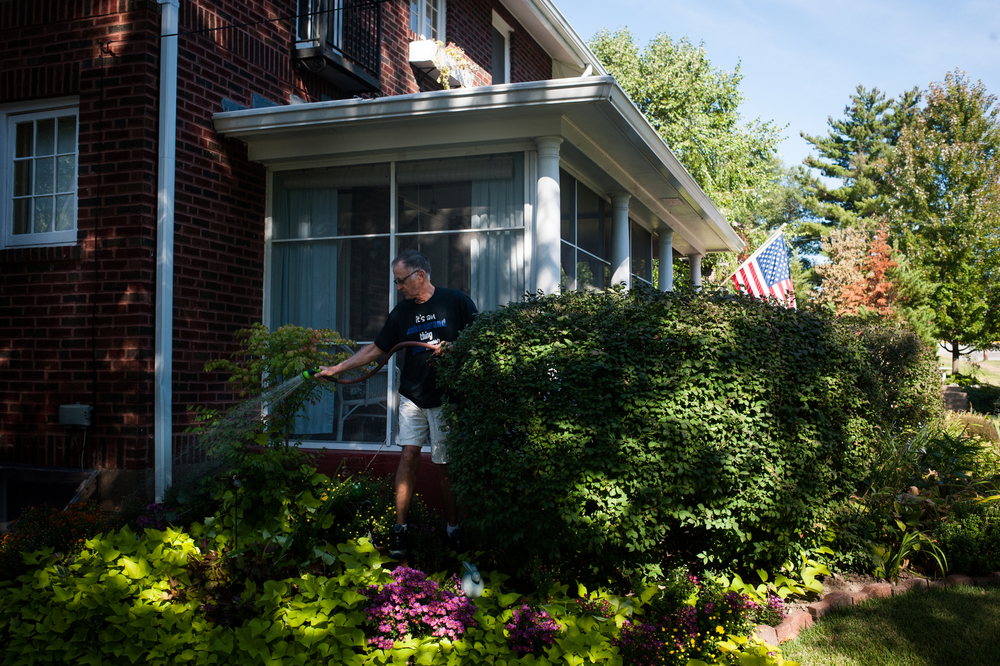 Ank Ankenbrand waters the lush gardens of his home in Historic East Ferguson, an area rarely targeted by code enforcement officers.