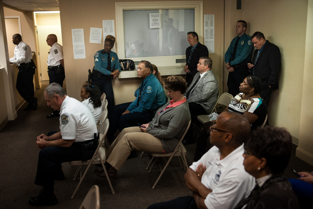 Members of the Ferguson Police Department watch as a member of the department receives an award at a city council meeting for rescuing a young girl who was found close to death. Also on the docket for the evening, as usual in the year after the protests, were issues related to federal accusations against the police department and city's behaviors.