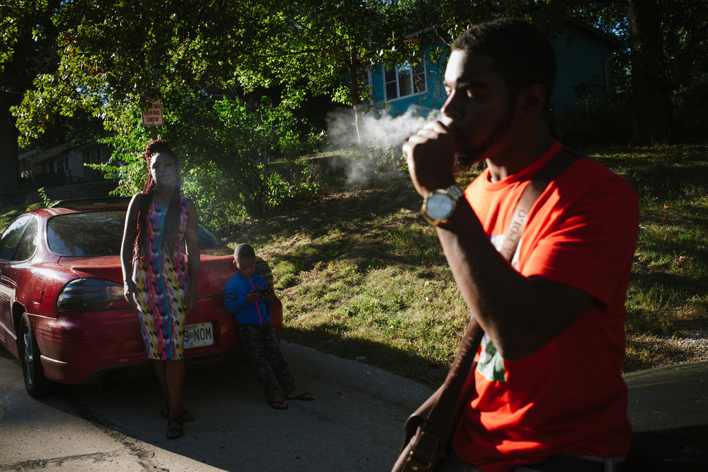 A woman and her son watch as Meech smokes a blunt the night before the funeral of their friend Darnell Smith.