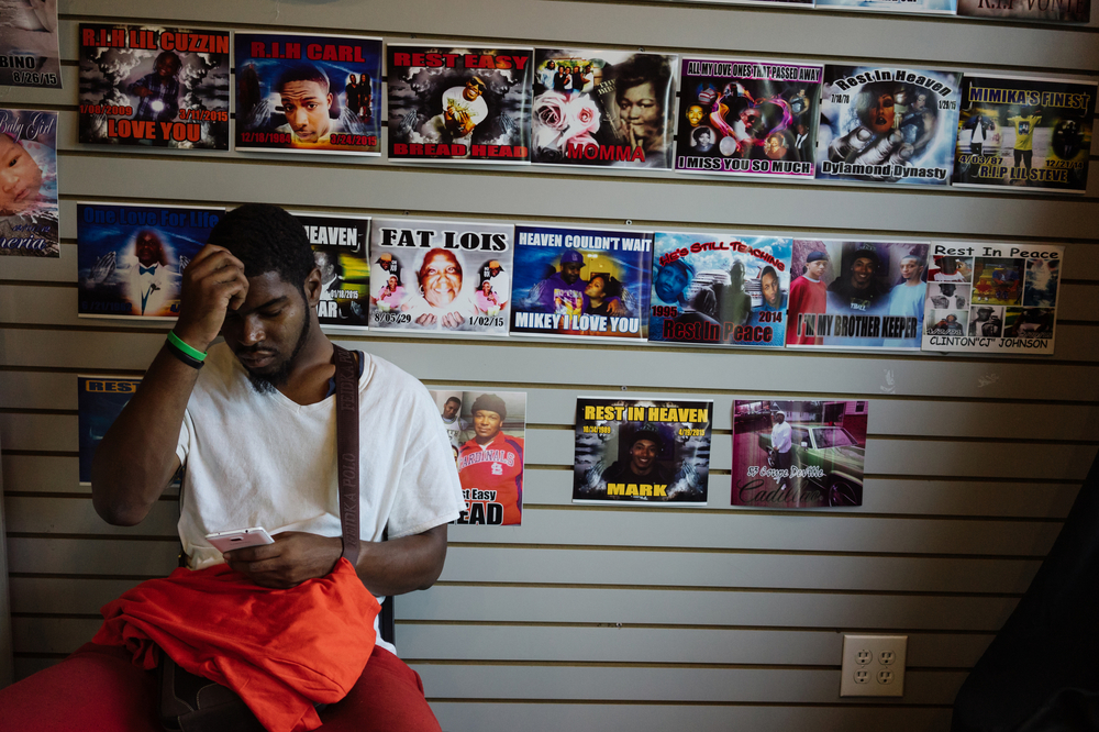 Posters of memorials are pasted to the wall at a local business that specializes in printing memorial t-shirts, a large portion of which are for young men who have been killed by gun violence in Ferguson and surrounding neighborhoods.