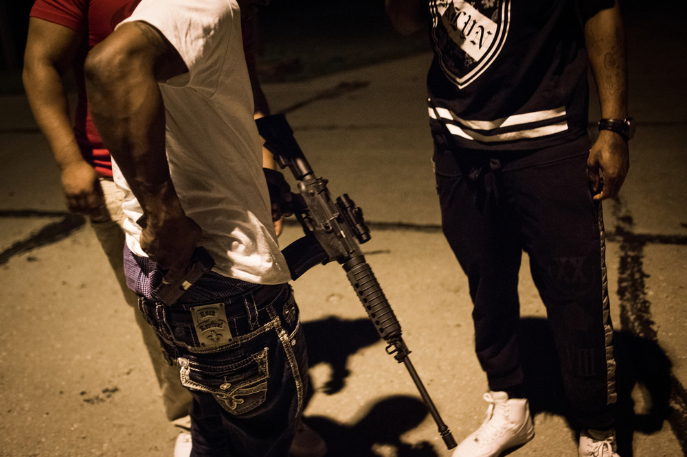 Members of Fatty Gang compare guns and hang out on a street while waiting for the start of the Floyd Mayweather/Manny Pacquiao fight later that evening. All the guns shown here are legally owned, though one of the group owns a number of illegal weapons despite felony gun possession convictions.