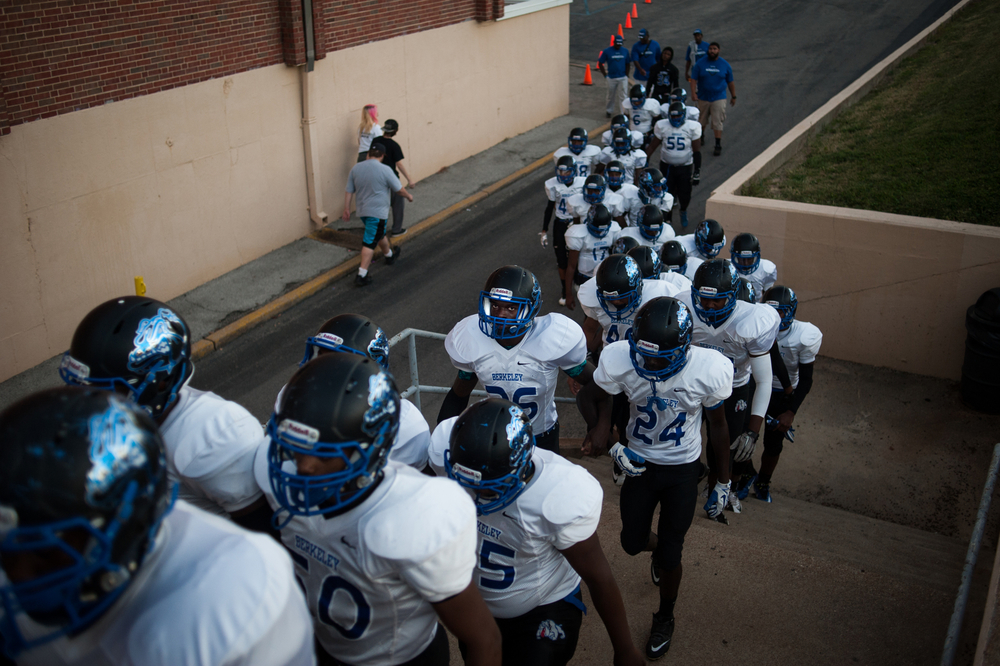 Members of the McCluer South-Berkeley football team make their way to the field at an away game against opponents at a school some distance across the city. The team is composed of all black students, which is similar to the makeup of their school itself.