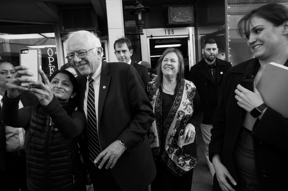A woman grabs Democratic presidential candidate Bernie Sanders for a selfie as he and his wife Jane, center, leave a campaign event at a local campaign office in Muscatine, Iowa on January 29.