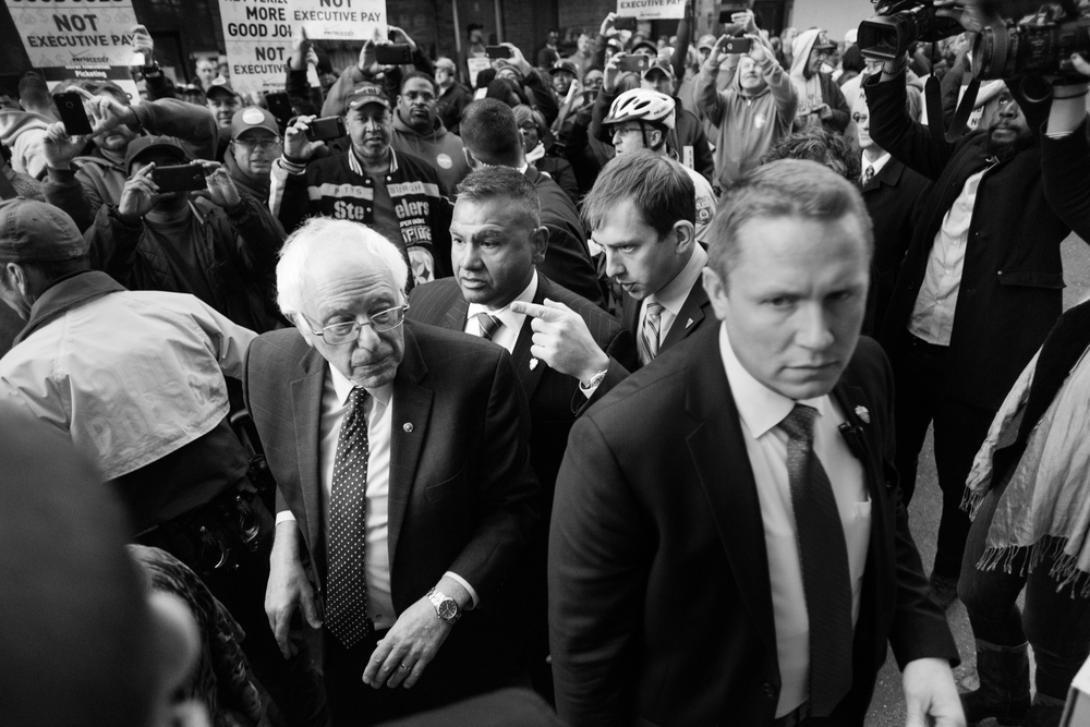 Shannon Jackson, aide to Democratic presidential candidate Bernie Sanders, speaks to Sanders and the lead Secret Service agent as they head through a crowd to speak to a Communication Workers of America protest in Philadelphia, Pennsylvania on April 6.