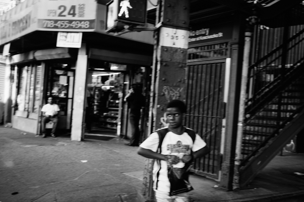 A boy crosses Broadway toward Bedford-Stuyvesant after stopping in a bodega in Bushwick.