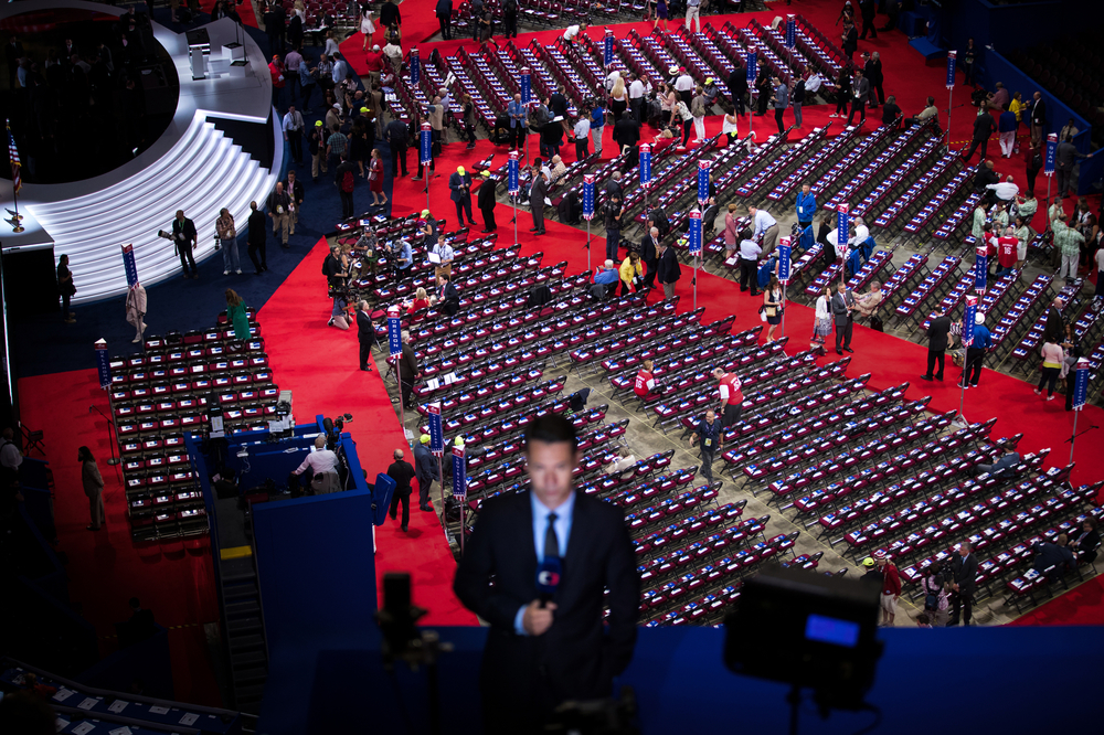 A television reporter does a standup as people are seen on the floor of the Republican National Convention at the Quicken Loans Arena in Cleveland, OH.