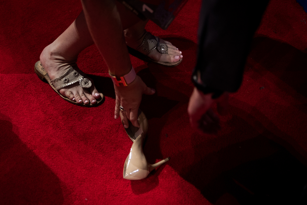 A woman picks up a shoe that fell out of her bag while walking the floor during the first day of the Republican National Convention in Cleveland, OH.