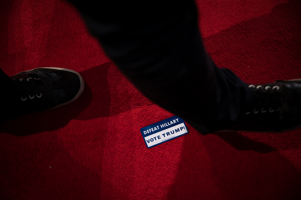 A man walks over an anti-Hillary Clinton sticker on the last night of the Republican National Convention in Cleveland, OH.