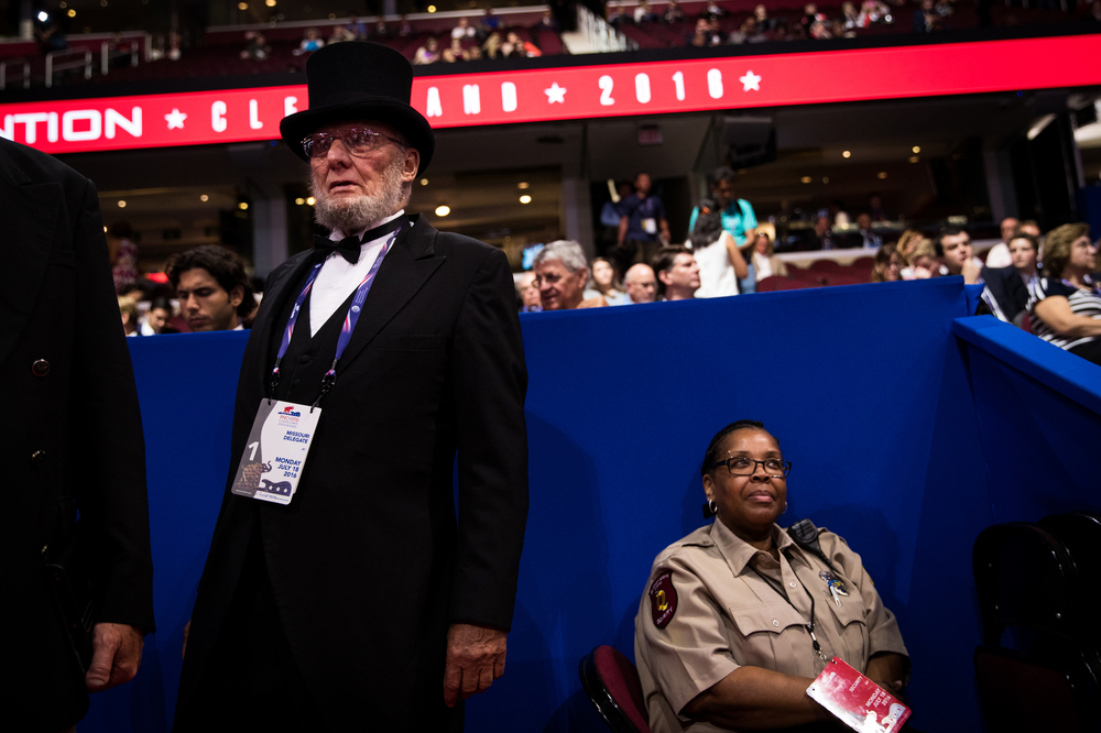 A Missouri delegate, dressed as former U.S. President Abraham Lincoln, and a security guard watch the crowd of the Republican National Convention in Cleveland, OH.