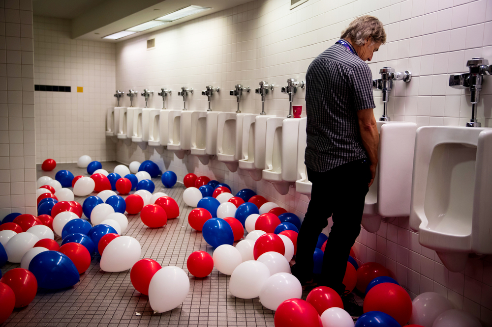 A man uses a urinal as balloons fill the floor of a bathroom on the last night of the Republican National Convention in Cleveland, OH.