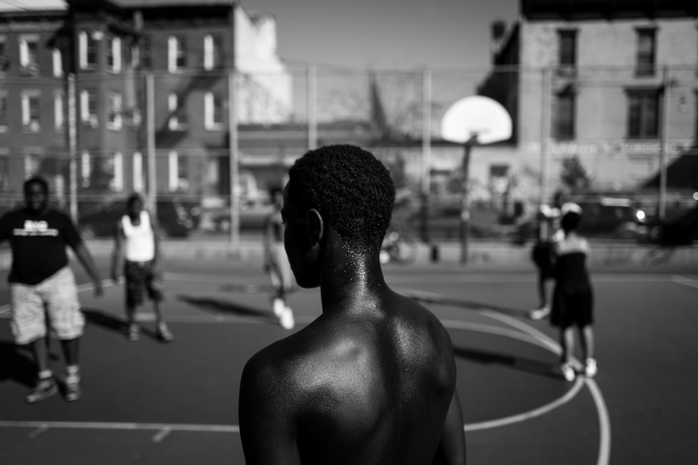 A young man pauses during a game of streetball at the park in Bushwick, NY.