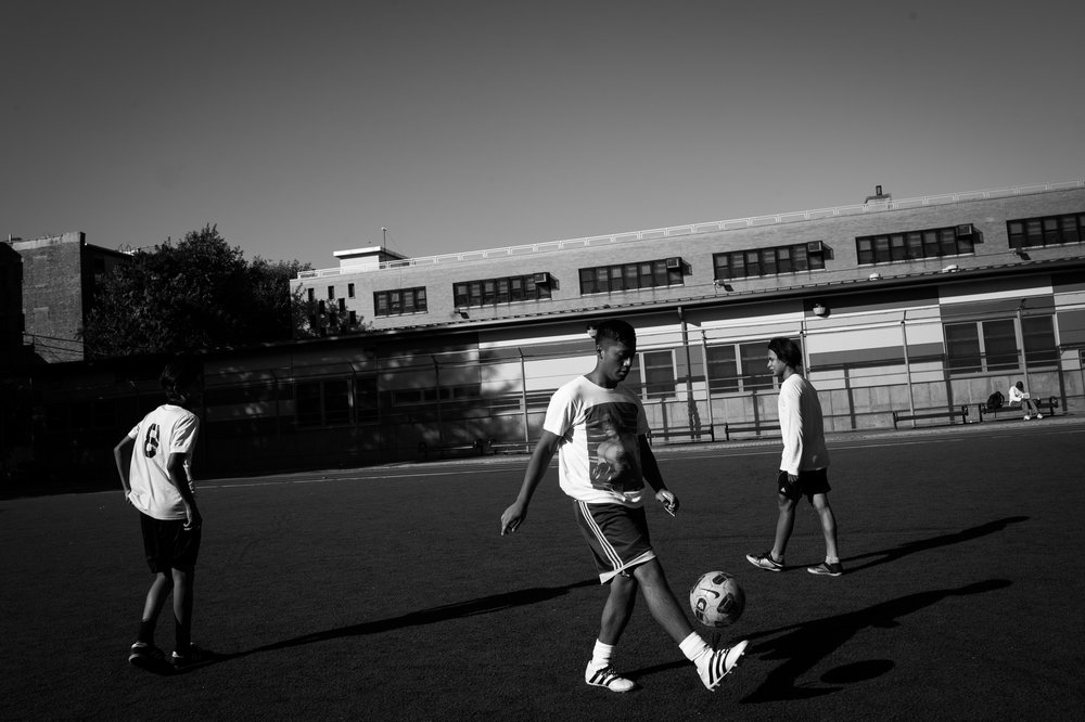 Jay William plays soccer with friends at a park behind P.S. 274 Kosciusko School in Bushwick, NY.