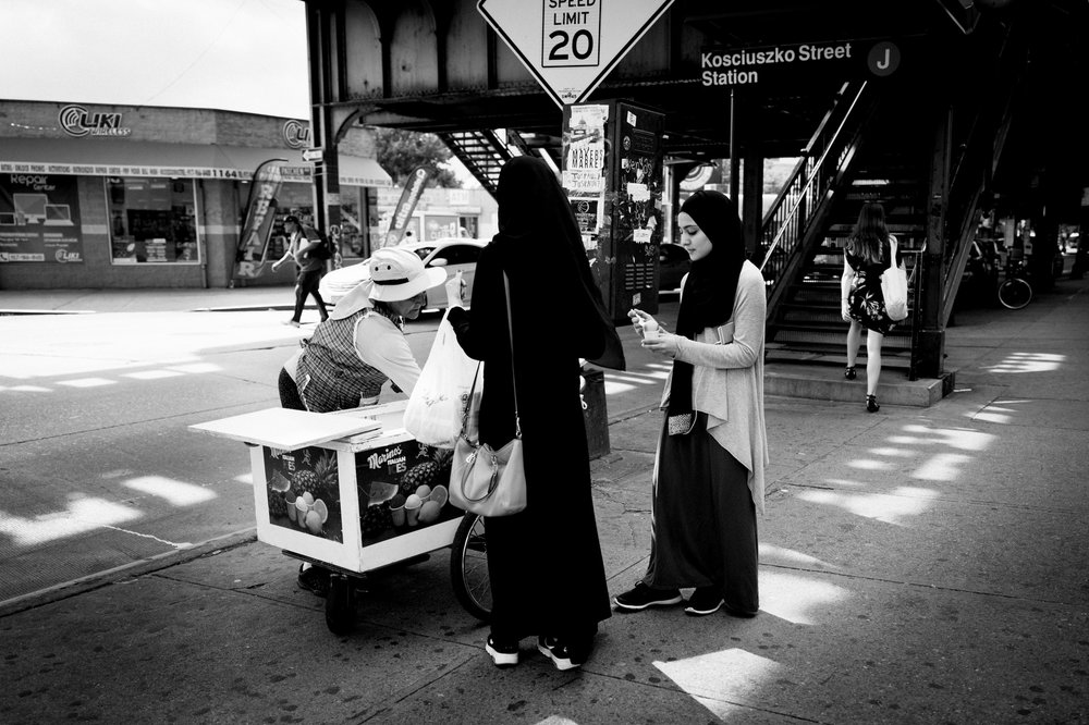 Two young women buy piragua (Puerto Rican shaved ice) from a traveling street vendor on Broadway in Bushwick, NY.