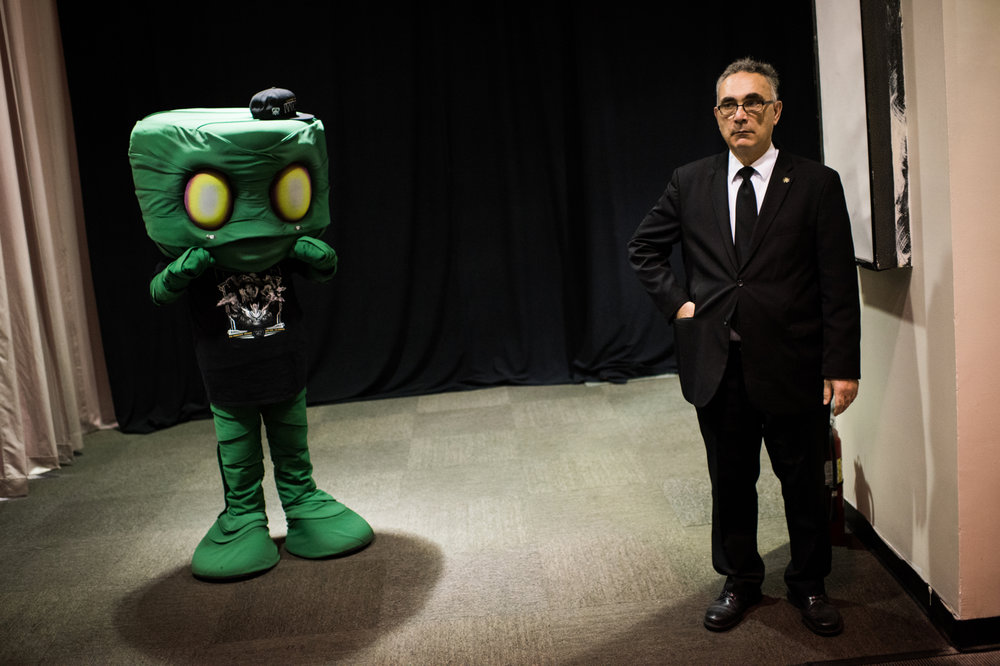 A security guard stands next to a person cosplaying as Amumu, a champion from League of Legends.