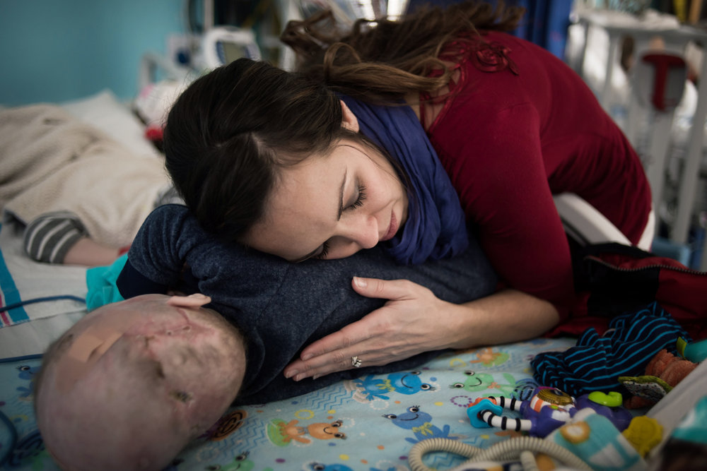Nicole McDonald holds her son Anias as she rubs his back in their hospital room at Montefiore Children's Hospital in The Bronx, New York, N.Y. on December 14, 2016.